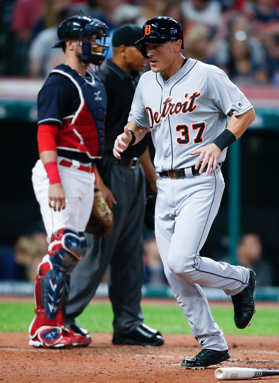 . Detroit Tigers\' Jim Adduci scores past Cleveland Indians\' Yan Gomes on a double by JaCoby Jones during the fourth inning of a baseball game, Friday, Sept. 14, 2018, in Cleveland. (AP Photo/Ron Schwane)
