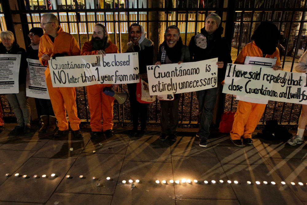 Description of . Campaigners gather outside the U.S. Embassy in London, holding various signs against the prison and wearing US President Obama masks, to mark the 11th anniversary of the opening of Guantanamo Bay U.S. prison in eastern Cuba, Friday, Jan. 11, 2013. (AP Photo/Sang Tan)