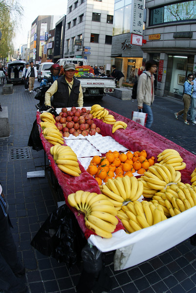 """Korean man with bananas and other fruit."""