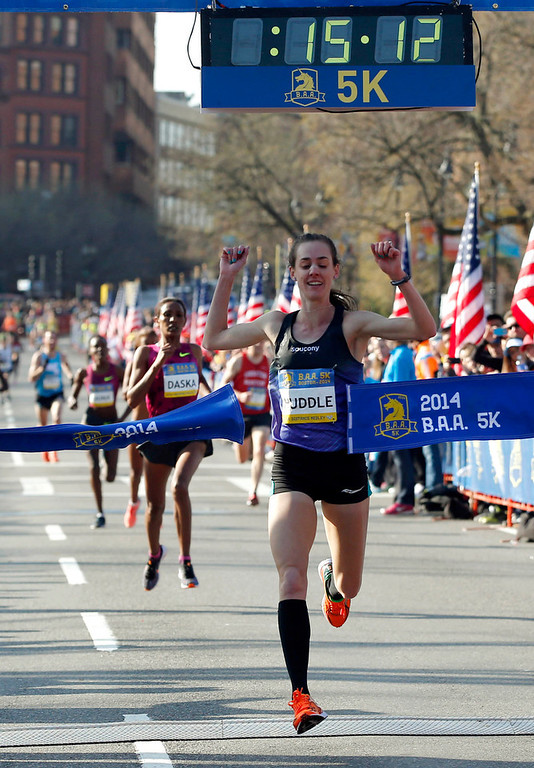 . Molly Huddle, of Providence, R.I., breaks the tape to win the women\'s division in the 5-kilometer run Saturday, April 19, 2014, in Boston in advance of Monday\'s 118th Boston Marathon. (AP Photo/Elise Amendola)