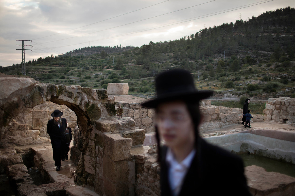 . Ultra-Orthodox Jews collect water to make \'matza\' or unleavened bread, during the Maim Shelanu Ceremony on a mountain spring in Jerusalem, Tuesday, April 12, 2016. The water is used to prepare traditional unleavened bread for Passover Holiday. (AP Photo/Oded Balilty)