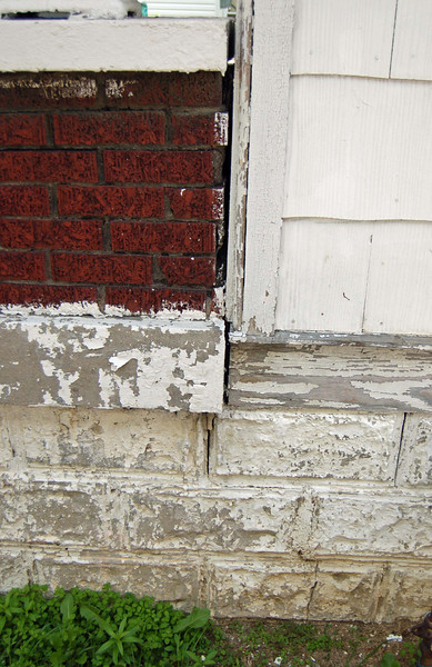 Example of paint failure on wood trim and foundation.