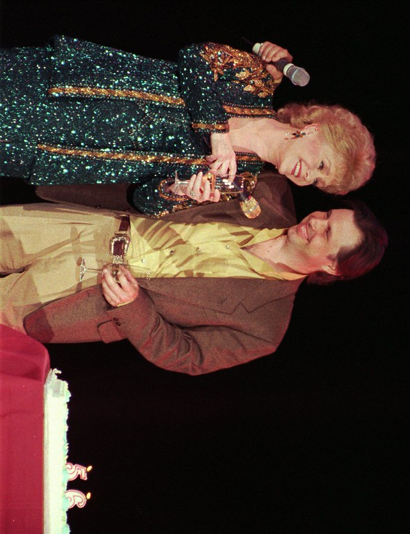 """. Debbie Reynolds, left, celebrates her 65th birthday on stage as her son, Todd Fisher, presents her with a cake following her evening variety show, Tuesday night, April 1, 1997, at the Debbie Reynolds Hotel in Las Vegas. Reynolds had a busy 64th year, starring in the critically acclaimed Albert Brooks film \""""Mother,\"""" as well as opening her new variety show. Reynolds joked around with Fisher, changing the position of the candles on the cake. (AP Photo/Lennox McLendon)"""