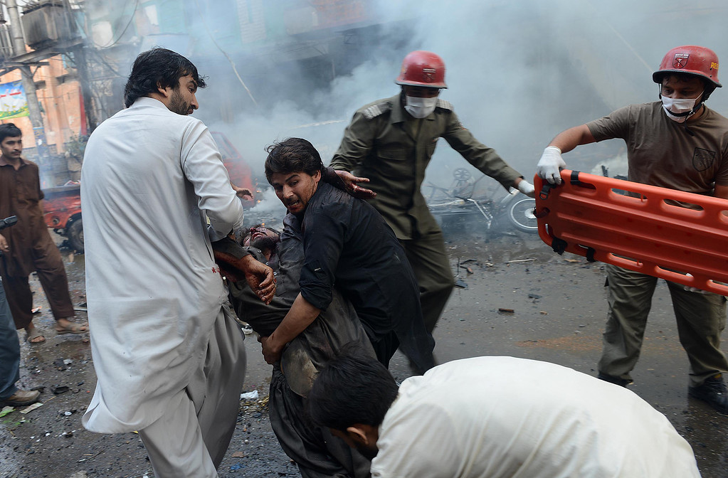 . Pakistani men carry an injured blast victim at the site of a bomb explosion in the busy Kissa Khwani market in Peshawar on September 29, 2013.  AFP PHOTO /  A.  MAJEED/AFP/Getty Images