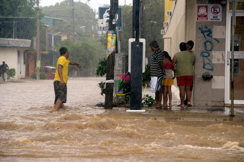 . People stand at the corner of a flooded street caused by heavy rains brought by Tropical Storm Manuel in Acapulco, Mexico, Monday Sept. 16, 2013. Tropical Storm Ingrid and remnants of Tropical Storm Manuel drenched Mexico\'s Gulf and Pacific coasts, flooding towns and cities in a national emergency that federal authorities say has caused at least 34 deaths. (AP Photo/Bernandino Hernandez)