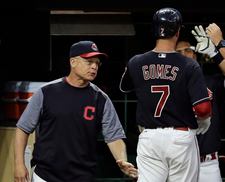 . Cleveland Indians acting manager Brad Mills, left, congratulates Yan Gomes after Gomes hit a solo home run off San Diego Padres relief pitcher Jose Torres during the sixth inning of a baseball game, Thursday, July 6, 2017, in Cleveland. (AP Photo/Tony Dejak)