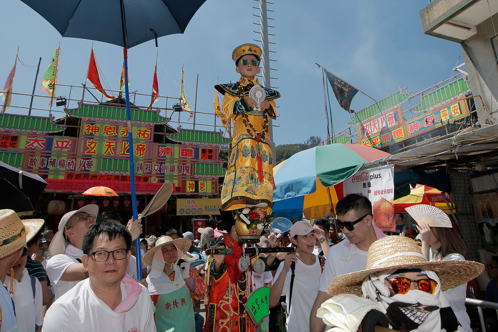 . A child dressed in a traditional Chinese costume floats in the air, supported by a rig of hidden metal rods, during a parade on the outlying Cheung Chau island in Hong Kong to celebrate the Bun Festival Tuesday, May 22, 2018. Bun Festival, the Taoist God of the Sea, is worshipped and evil spirits are scared away by loud gongs and drums during the procession. The celebration includes bun scrambling, parades, opera performances, and children dressed in colorful costumes. (AP Photo/Kin Cheung)