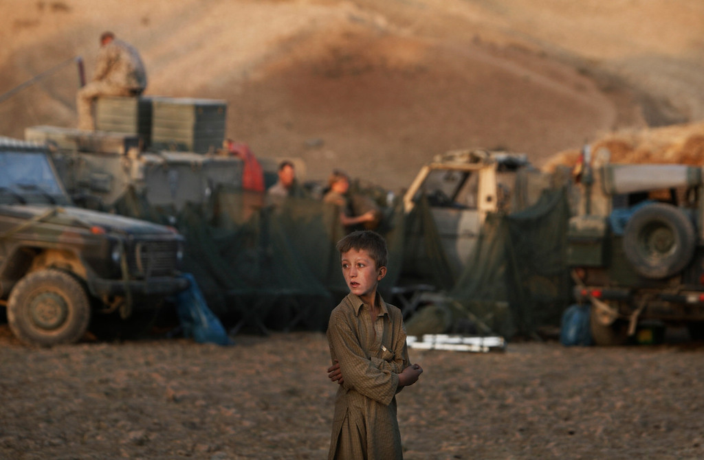 . In this Monday, Sept. 14, 2009 file photo made by Associated Press photographer Anja Niedringhaus,an Afghan boy looks on as German ISAF soldiers prepare a temporary camp to overnight during a long term patrol in the mountainous region of Feyzabad, east of Kunduz, Afghanistan. (AP Photo/Anja Niedringhaus, File)