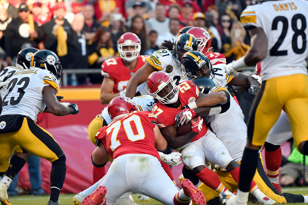 . Pittsburgh Steelers players stop Kansas City Chiefs running back Kareem Hunt (27) during the second half of an NFL football game in Kansas City, Mo., Sunday, Oct. 15, 2017. (AP Photo/Ed Zurga)