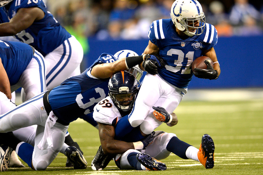 . Outside linebacker Danny Trevathan (59) of the Denver Broncos gets through the line to stop running back Donald Brown (31) of the Indianapolis Colts at Lucas Oil Stadium.  (Photo By Joe Amon/The Denver Post)