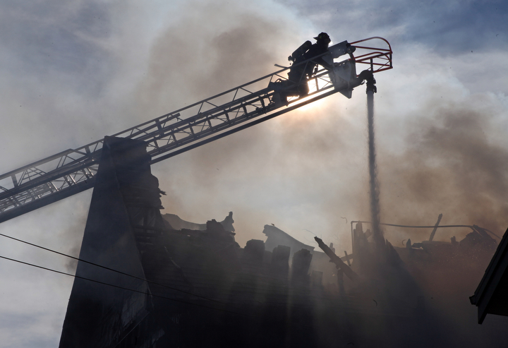 . Oakland firefighters battle a fully involved house fire at the three-story wood-frame house in the 2000 block of East 26th Street about 9 a.m. in Oakland, Calif., on Tuesday, Jan. 15, 2013.  The owner was not home when the fire started, said Battalion Chief Jenny Ray.(Laura A. Oda/Staff)