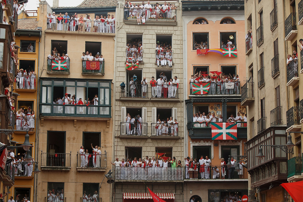 . Revellers stand on balconies watching the opening and the firing of the \'Chupinazo\' rocket which starts the 2014 Festival of the San Fermin Running of the Bulls on July 6, 2014 in Pamplona, Spain. The annual Fiesta de San Fermin, made famous by the 1926 novel of US writer Ernest Hemmingway entitled \'The Sun Also Rises\', involves the daily running of the bulls through the historic heart of Pamplona to the bull ring.  (Photo by Pablo Blazquez Dominguez/Getty Images)