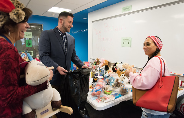 12/17/18 Wesley Bunnell | Staff Glenda Negron, R, picks out toys for ages two, three and twelve year old children at the New Britain Housing Authority's 9th annual toy donation on Monday afternoon with the help of Self Sufficiency Coordinator Nancy Copeland and Senior Family Self Sufficiency Coordinator Eric Montanile.