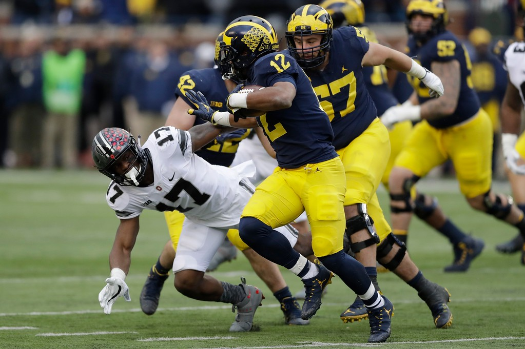 . Michigan running back Chris Evans (12) runs around Ohio State linebacker Jerome Baker (17) during the first half of an NCAA college football game, Saturday, Nov. 25, 2017, in Ann Arbor, Mich. (AP Photo/Carlos Osorio)
