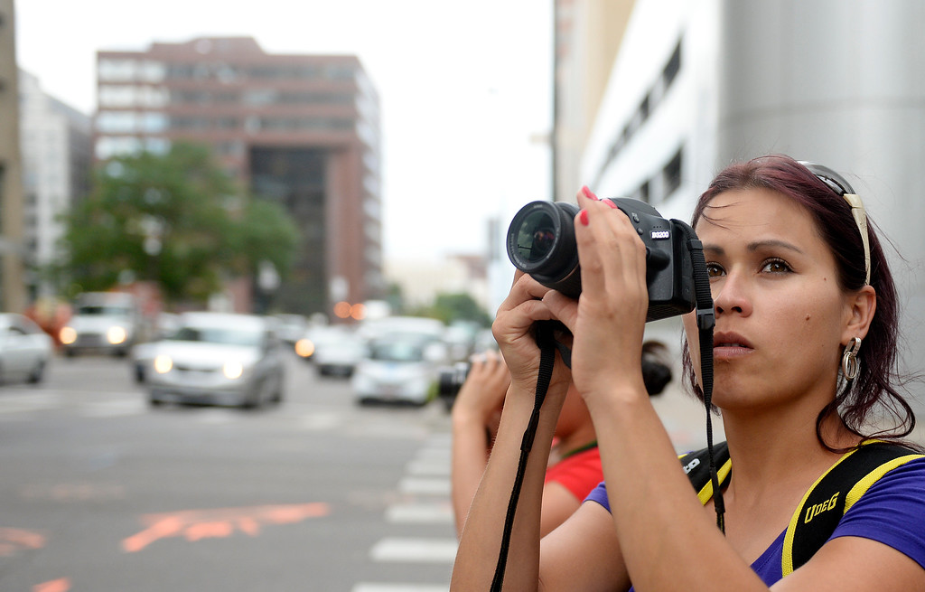 """. Colorado Public TV Channel 12 is sponsoring a photography class  \""""Picture Me Here\"""" as part of the it\'s American Graduate initiative.  Students  Sonia Muñoz, and Maricela Rivera, background, both originally from Mexico photographed in downtown Denver along Lincoln Street. The class was held at Emily Griffith Technical School in Denver on Tuesday July 21, 2015.   (Photo by Cyrus McCrimmon/The Denver Post )"""