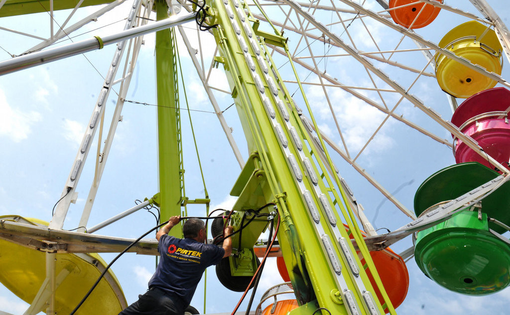 . A workman works on some electrical work at the base of the ferris wheel in the Midway. (Pioneer Press: John Doman)