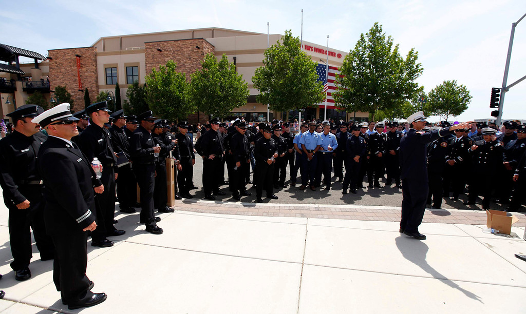 . Los Angeles firefighters gather outside a memorial for the fallen members of Prescott Fire Department\'s Granite Mountain Hotshots team in Prescott Valley, Arizona July 9, 2013.  REUTERS/Mike Blake