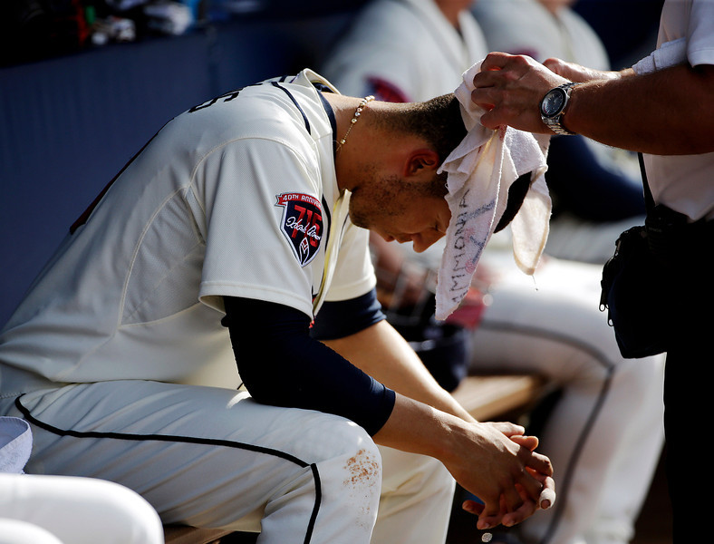 . Atlanta Braves\' Andrelton Simmons has a wet towel draped over his head by trainer Jim Lovell as he sits in the dugout in the fourth inning of a baseball game against the Colorado Rockies, Saturday, May 24, 2014, in Atlanta. (AP Photo/David Goldman)