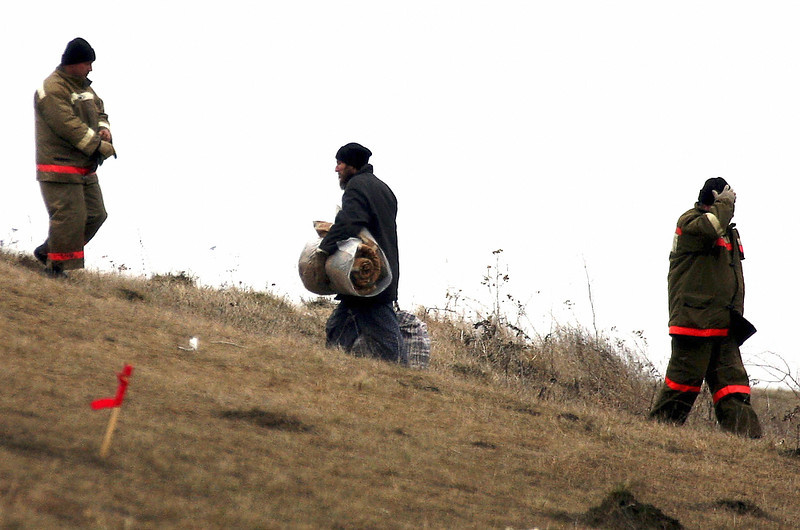 ". A member of a Russian doomsday sect carries his belongings after leaving the muddy cave in Nikolskoye on April 2, 2008. Three of the last 14 members of a Russian doomsday sect left their muddy cave on Wednesday after five months barricaded underground waiting for the Apocalypse, an AFP reporter saw. ""Now there are only 11 left,\"" deputy Penza Region governor Oleg Melnichenko told journalists at the site. \""All the children are now above ground.\""  DMITRY KOSTYUKOV/AFP/Getty Images"