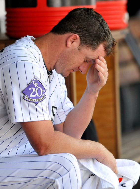 . Colorado Rockies starting pitcher Roy Oswalt sits in the dugout after being pulled during the fifth inning of a baseball game against the St. Louis Cardinals, Thursday, Sept. 19, 2013, in Denver. (AP Photo/Jack Dempsey)