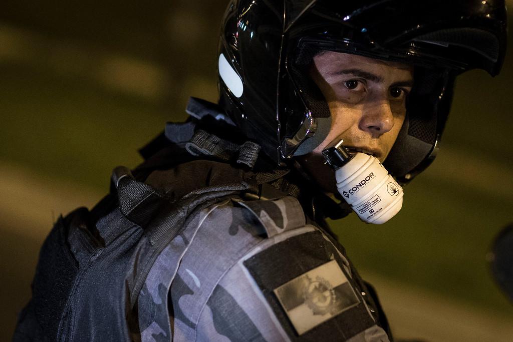 . A riot police officer uses his front teeth to hold onto to a non-lethal grenade during an anti-government protest near the Cidade de Deus, or City of God slum, in Rio de Janeiro, Brazil, Friday, June 21, 2013.  (AP Photo/Felipe Dana)
