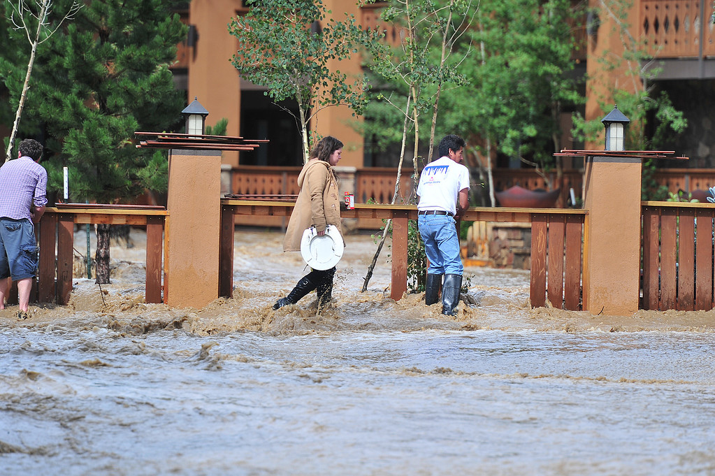 . People carry what they can from businesses on West Elkhorn Avenue as the Fall River covers the west end of downtown Estes Park. Walt Hester/Estes Park Trail-Gazette