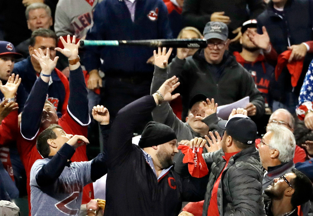 . Fans get out of the way after Toronto Blue Jays\' Edwin Encarnacion let go of his bat during the eighth inning in Game 1 of baseball\'s American League Championship Series against the Cleveland Indians in Cleveland, Friday, Oct. 14, 2016. (AP Photo/Matt Slocum)