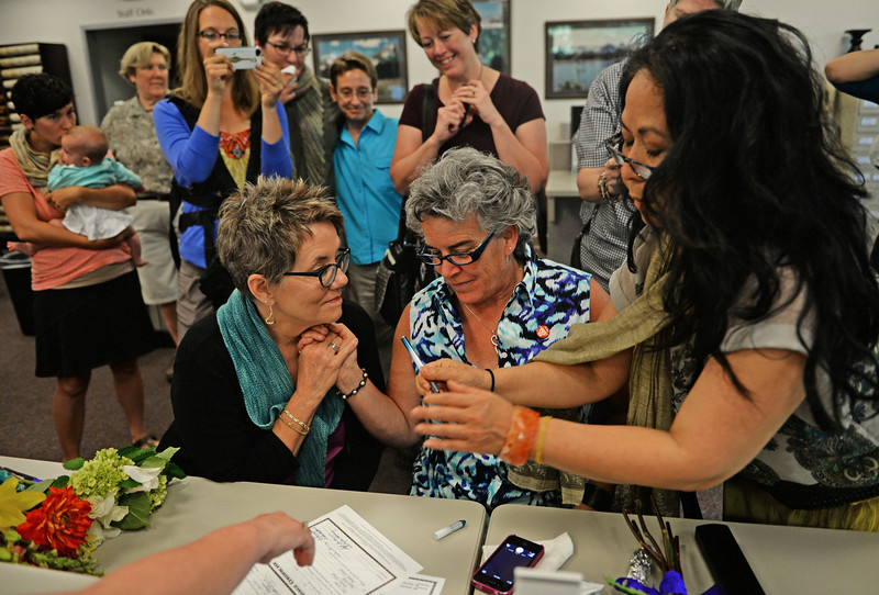 . Newlyweds Angie Holley, left, and Bylo Farmer, of Boulder, holds hands as they get the final signatures on their marriage license issued this morning at the Boulder County Clerk and Recorder\'s Office, June 26, 2014. Boulder County issued five more marriage licences to same-sex couples in the first hour that the Clerk and Recorder\'s Office in Boulder was open. (Photo by RJ Sangosti/The Denver Post)