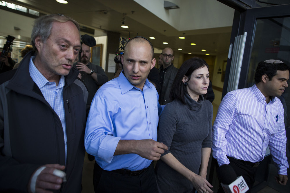Description of . Bayit Yehudi (Jewish Home) party leader Naftali Bennett speaks with the media alongside his wife after casting his vote in the Israeli General Election on January 22, 2013 in Ra'anana, Israel. The latest opinion polls suggest that current Prime Minister Benjamin Netanyahu will return to office, albeit with a reduced majority.  (Photo by Ilia Yefimovich/Getty Images)