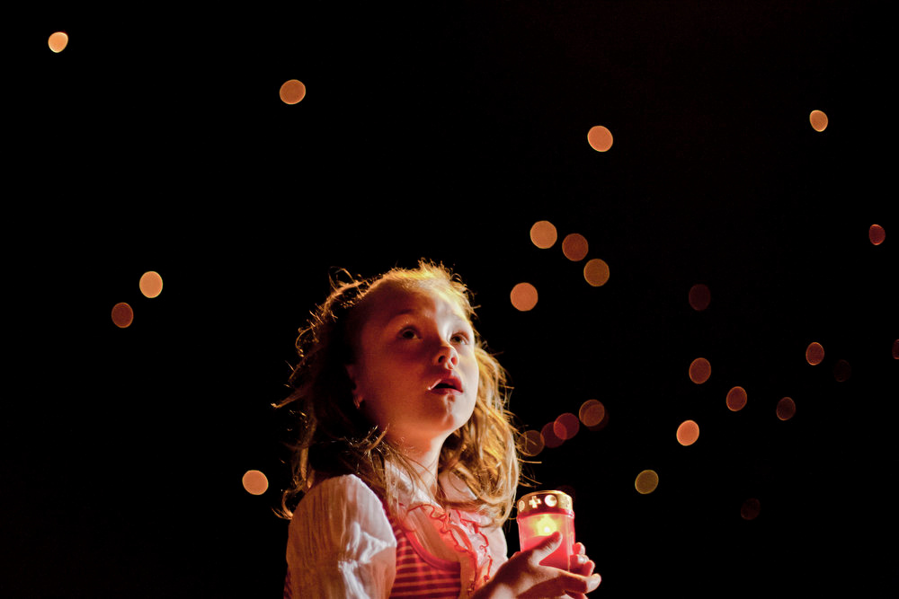 . Rebeca Blaha, 6 years old, holds a candle while watching lanterns fly, after the orthodox Easter religious service in the Black Sea port of Mangalia, Romania, Sunday, May 5, 2013. Up to 7.000 people attended the service and 5.000 lanterns were launched, according to local media.(AP Photo/Bogdan Chesaru)