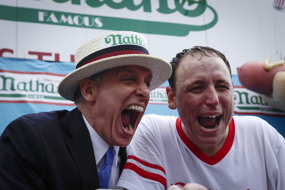 . Joey Chestnut (R) and George Shea celebrate after Chestnut wins the 98th annual 2014 Nathan\'s Famous Hot Dog Eating Contest at Coney Island on July 4, 2014 in the Brooklyn borough of New York City.  Chesnut won his eighth straight Nathan\'s Hot Dog Eating Contest with 61 hot dogs. (Photo by Kena Betancur/Getty Images)