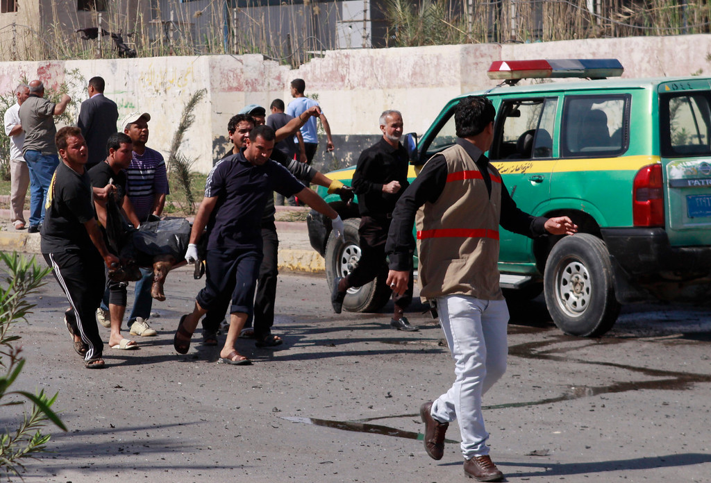 . People evacuate the body of a car bomb victim following an attack near the municipal building in the Shiite stronghold of Sadr City, Baghdad, Iraq, Tuesday, March 19, 2013. (AP Photo/ Karim Kadim)