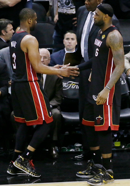 . Miami Heat guard Dwyane Wade (3) and LeBron James (6) slap hands on the sideline during the second half in Game 5 of the NBA basketball finals against the San Antonio Spurs, on Sunday, June 15, 2014, in San Antonio. The Spurs won the NBA championship 104-87. (AP Photo/Tony Gutierrez)