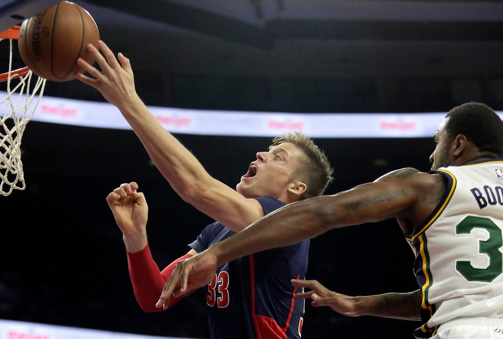 . Detroit Pistons\' Jonas Jerebko (33), of Sweden, goes to the basket past Utah Jazz\'s Trevor Booker during the second half of an NBA basketball game Sunday, Nov. 9, 2014, in Auburn Hills, Mich.  The Jazz defeated the Pistons 97-96. (AP Photo/Duane Burleson)