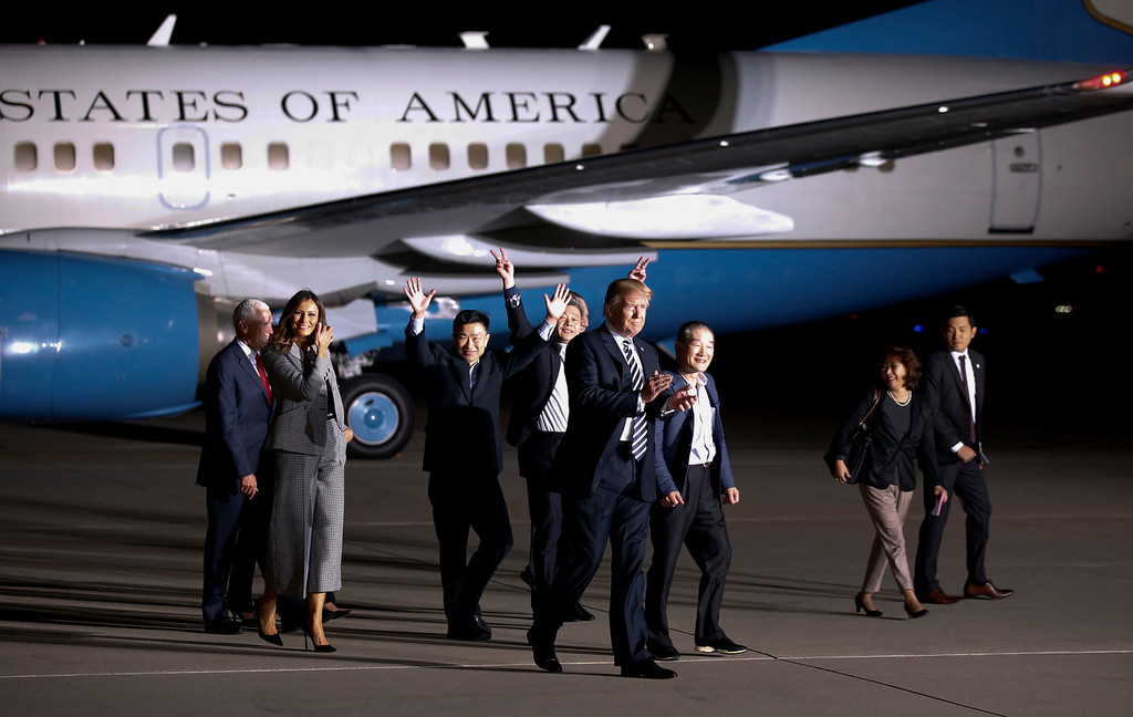 . President Donald Trump and first lady Melania Trump walk with former North Korean detainees Tony Kim, third from left, Kim Hak Song, and Kim Dong Chul, third from right, and others, upon their arrival, Thursday, May 10, 2018, at Andrews Air Force Base, Md. The three Korean-Americans were greeted by Trump beneath a giant American flag after they returned to the mainland U.S. early Thursday. (AP Photo/Alex Brandon)
