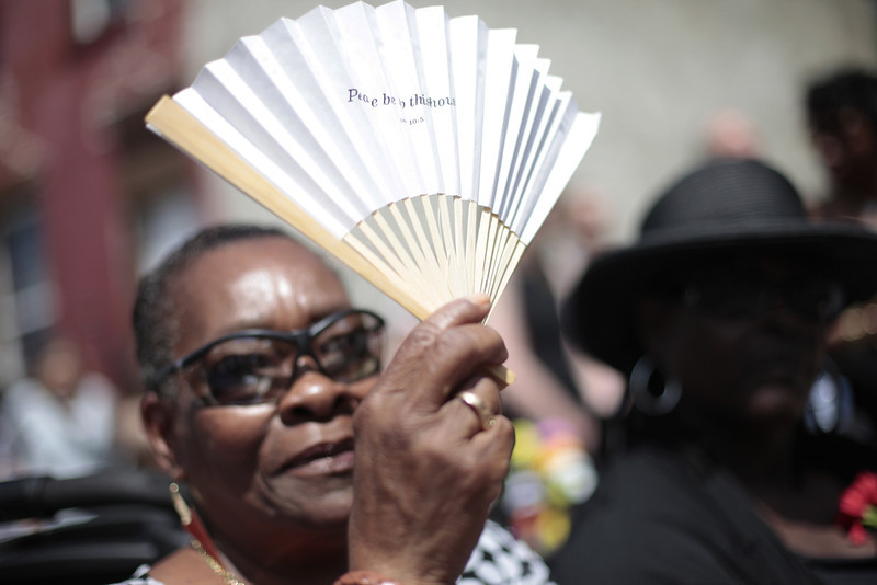 ". Ernestine Eltzy holds a commemorative fan during a ""home going\"" service at the site of an abandoned home in the impoverished Mantua section Philadelphia on Saturday, May 31, 2014. The cultural and memorial project called �Funeral for a Home� celebrated the dilapidated row house\'s colorful life before it was knocked down. Organizers from Temple University said it was an effort to commemorate neighborhood history in a city where about 600 houses are torn down each year and 25,000 others sit vacant. (AP Photo/Jessica Kourkounis)"