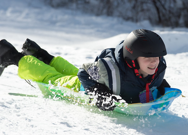 03/04/19 Wesley Bunnell | Staff Chris Stager, age 13, smiles as he sleds his way down a hill at Page Park on Monday afternoon with friends.