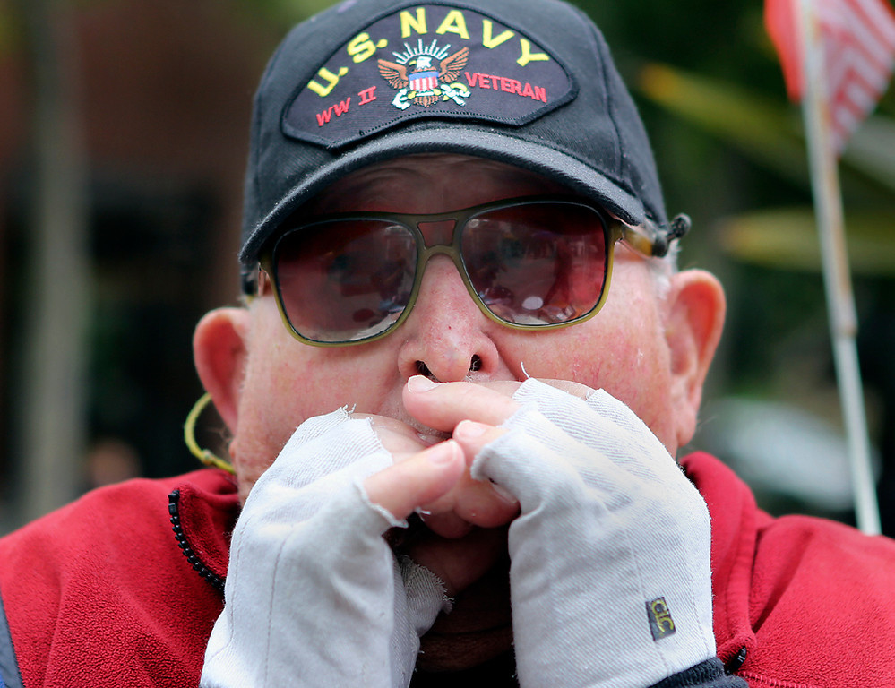 . World War II Veteran Maurice Ricketts plays the harmonica with members of the Disabled American Veterans Chapter 52 at Memorial Plaza in downtown Santa Cruz on Monday. (Kevin Johnson/Sentinel)