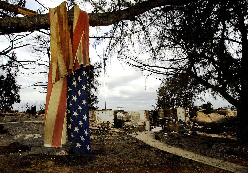 . A tattered and torn flag lies tangled in a tree on the front lawn of a destroyed home Thursday, Oct. 30, 2003 in Crest, Calif. Numerous homes were destroyed by the Cedar Fire which continues to burn just outside San Diego. (AP Photo/Matt York)