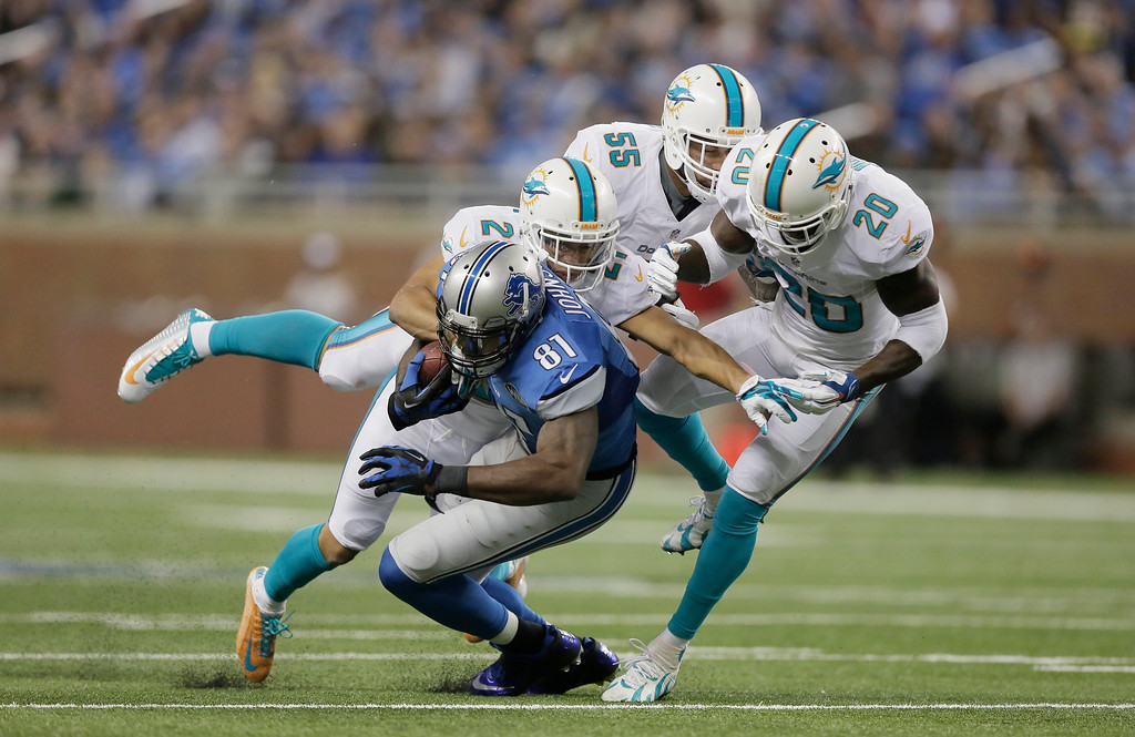 . Detroit Lions wide receiver Calvin Johnson (81) is stopped by Miami Dolphins cornerback Brent Grimes (21) during the first half of an NFL football game in Detroit, Sunday, Nov. 9, 2014. (AP Photo/Duane Burleson)