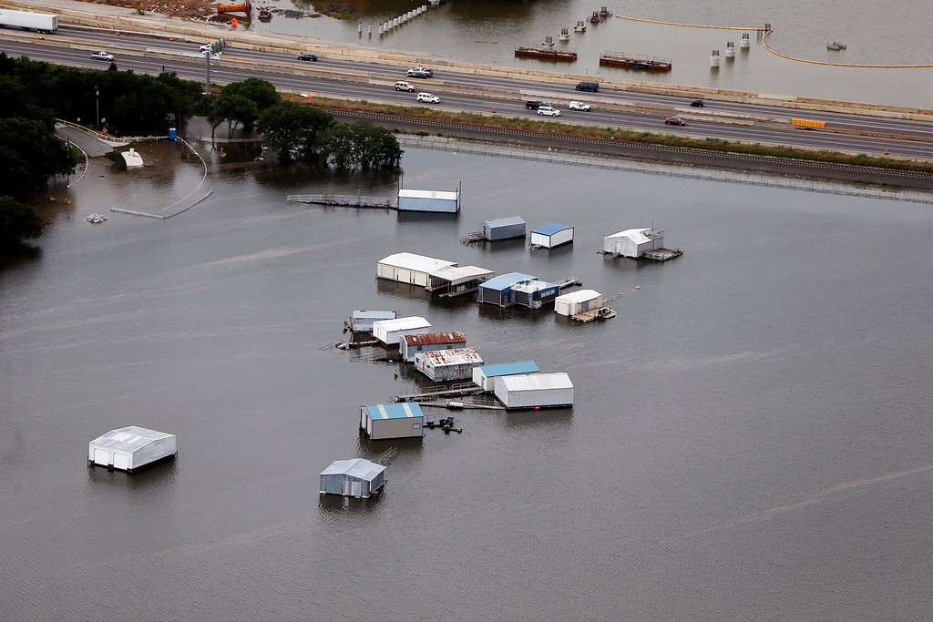 . A swollen Lake Lewisville forced boat house to break free from their moorings, Friday, May 29, 2015 in Lewisville, Texas. Floodwaters submerged Texas highways and threatened more homes Friday after another round of heavy rain added to the damage inflicted by storms. (AP Photo/Brandon Wade)