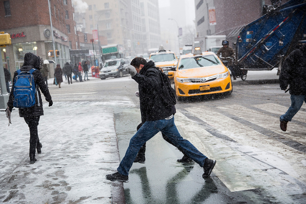 . Two people jump over a puddle during a snowstorm that is moving through the Northeast on January 21, 2014 in New York City.   (Photo by Andrew Burton/Getty Images)