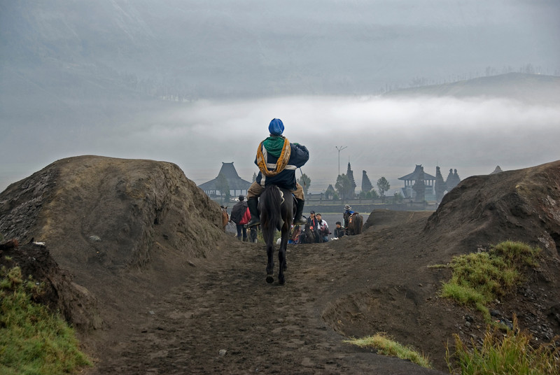 Man riding on a horse on the road to Mount Bromo