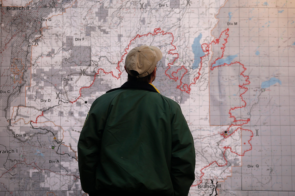 . A firefighter looks at the Rim Fire incident report map posted at the command post near Yosemite National Park, Calif., on Monday, Aug. 26, 2013.  (AP Photo/Jae C. Hong)