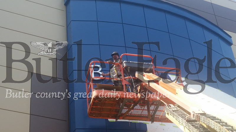 "Steve Peffer of Graphics Garage in Butler hangs the very first letter on the county government building's new blue badge on Sunday. The letters spell out ""Butler County Government Center."""