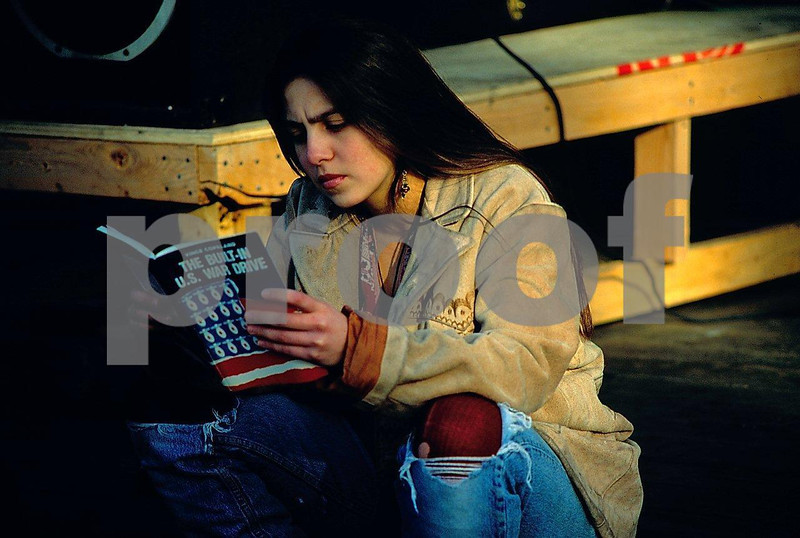 A young woman reads a book about the U.S. War Drive while attending a Feb. 1991 protest of the Gulf War.
