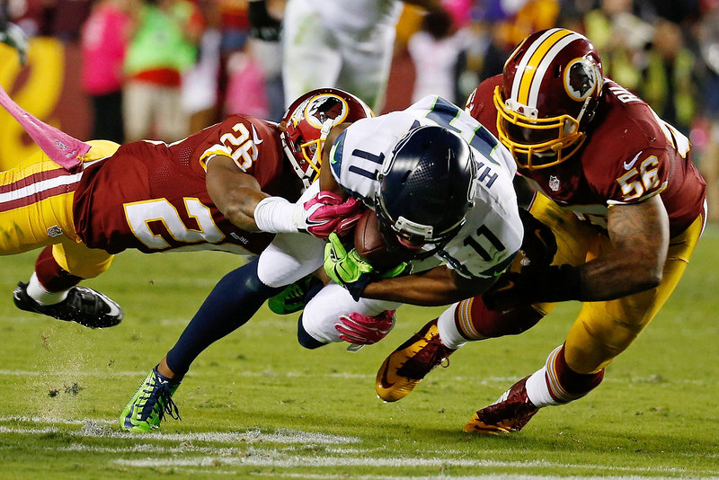 . Washington Redskins strong safety Bashaud Breeland (26) and inside linebacker Perry Riley (56) knock Seattle Seahawks wide receiver Percy Harvin (11) to the turf during the first half of an NFL football game in Landover, Md., Monday, Oct. 6, 2014. (AP Photo/Alex Brandon)