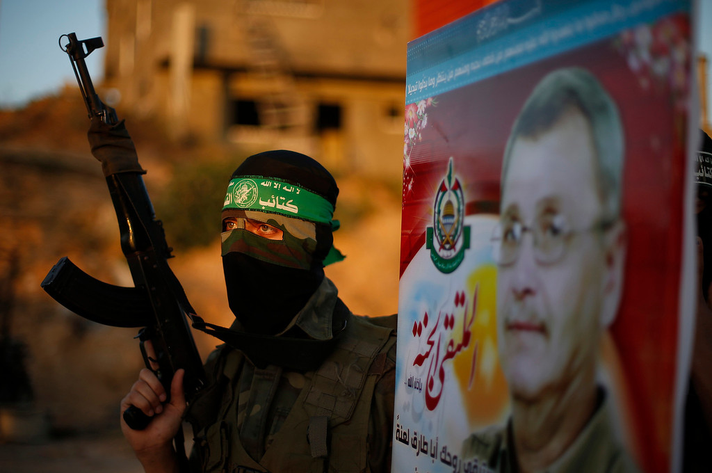 . A Hamas militant holds a poster of Maysara Abu Hamdeya before a protest in the northern Gaza Strip April 2, 2013. Israeli prison guards fired tear gas to quell disturbances by Palestinian inmates on Tuesday after a prisoner serving a life sentence over an attempt to bomb an Israeli cafe died of cancer. Maysara Abu Hamdeya\'s death threatened to raise tensions in the Israeli-occupied West Bank, where Palestinians, who view jailed brethren as heroes in a fight for statehood, have held several protests in recent weeks in support of prisoners. REUTERS/Suhaib Salem