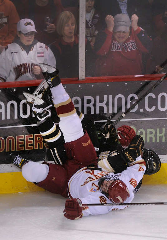 . DENVER, CO. - NOVEMBER 16: Denver defenseman Josiah Didier (4) slid into the boards with Western Michigan left wing Colton Hargrove (14) in the second period. The University of Denver hockey team hosted Western Michigan at Magness Arena Saturday night, November 16, 2013.  Photo By Karl Gehring/The Denver Post