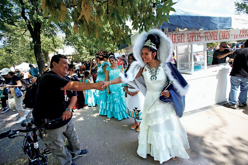 Artist Joseph Fragua of Jemez Pueblo shakes hands with La Reina, Elise Lopez y Leyba, during the 306th Fiestas de Santa Fe at the Plaza on Friday, September 6, 2019. Luis Sánchez Saturno/The New Mexican